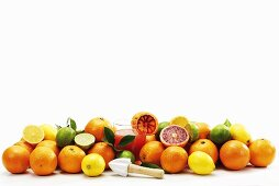 Assorted citrus fruits, glass of juice and lemon reamer