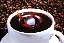 Sugar cube falling in cup of coffee