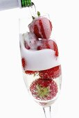 Pouring sparkling wine into glass of strawberries