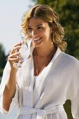 Woman in bathrobe drinking glass of water
