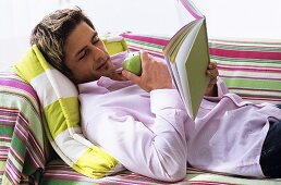 Young man lying on sofa, reading book, side view