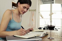 Young woman sitting at table with books, laptop and red wine