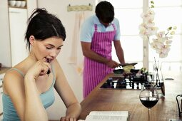 Woman working in kitchen, man cooking