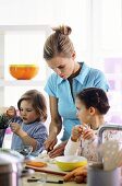 Mother and two children preparing meal in kitchen