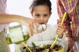 Parents with daughter preparing salad
