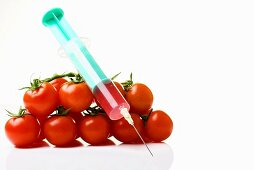 Syringe by bunch of tomatoes , close-up