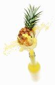 Pineapple juice splashing out of bottle