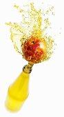 Apple juice splashing out of bottle