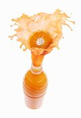 Mandarin orange juice splashing out of bottle