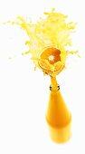 Orange juice splashing out of bottle