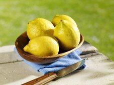 Several lemons in wooden bowl