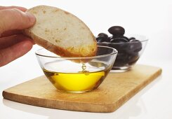 Hand dipping slice of white bread in olive oil