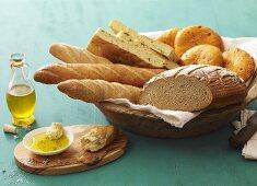 Assorted bread and bread rolls in bread basket, olive oil beside it