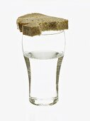 Glass of water and partly-eaten slice of bread