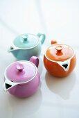 Three coloured teapots