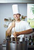 Laughing chef stirring pan