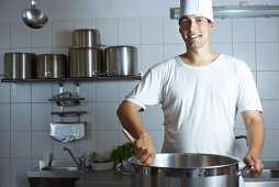 Chef stirring a pan on range