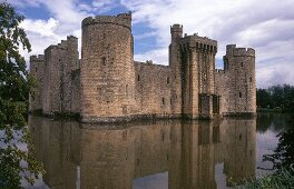 Bodiam Castle with massive stone walls and towers surrounded with water, UK