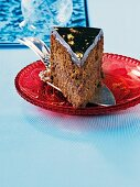 A slice of chocolate cake decorated with flakes of gold leaf