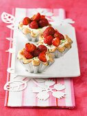 Three mascarpone and strawberry tartlets in silver cases on a plate