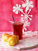 A glass of strawberry and rhubarb jelly with champagne and a croissant