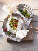 Noodles with cabbage, tomatoes and olives in parchment paper