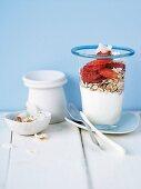 Yogurt with muesli and fresh strawberries for breakfast