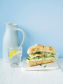 A fish burger with cucumber and a glass of water