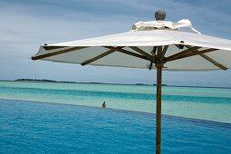 Parasol at swimming pool in front of sea, Dhigufinolhu island, Maldives