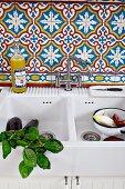 Weisses Keramik Spülbecken mit Basilikumzweigen und Gemüse, an Wand marokkanische Fliesen