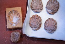 Bärentatzen (madeline-style cakes) being made: cakes being removed from moulds