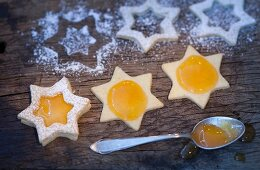 Star-shaped biscuits being spread with jam