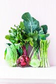 An arrangement of vegetables featuring beetroot, asparagus, pointed cabbage and kohlrabi
