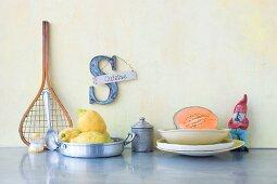 An arrangement featuring crockery, a garden gnome, fruit and a decorative letter S