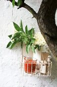 A basket of rhubarb and elderberry jam and elderflowers on a wall