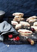 Crumbly marzipan and cherry biscuits on a baking tray