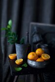 An arrangement of oranges in a bowl and on a stool