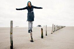 Woman wearing burberry coat balancing on stake at beach