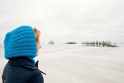 Contemplative blonde woman wearing coat and blue cap on beach, smiling