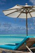 View of footbridge with umbrella and two women in sea, Anantara Dhigu island, Maldives