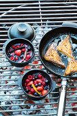 Berry compote in small pots and French toast in a pan on a barbecue