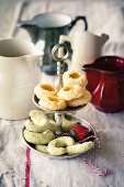 Mango doughnuts and cardamom and pistachio biscuits on a cake stand