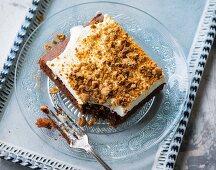 A slice of amaretto cake with cream and amarettini crumbs