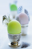 Coloured eggs and feathers in egg cups