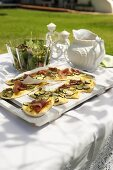 Tarte flambée with Parma ham and courgette on a table in a garden
