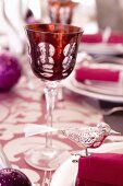 A red wine glass on table decorated for Christmas