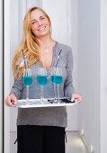 A woman serving blue drinks at Christmas time
