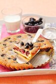 An almond tart with blueberries and icing sugar, sliced