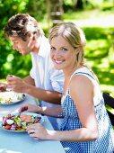 A couple eating salad in a garden