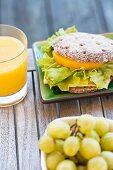 A pepper sandwich, grapes and orange juice